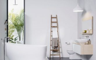 simple Scandinavian bathroom white bathtub with white ceramic tiled base freestanding stainless steel faucet mosaic tiled floors and wall wood ladder rack for towel wall mounted toilet in white