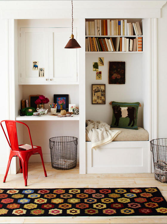 small built in alcove for study room and reading nook built in cabinet open shelves for books built in bench seat with futon multicolored area rug red plastic chair lightweight metal net basket