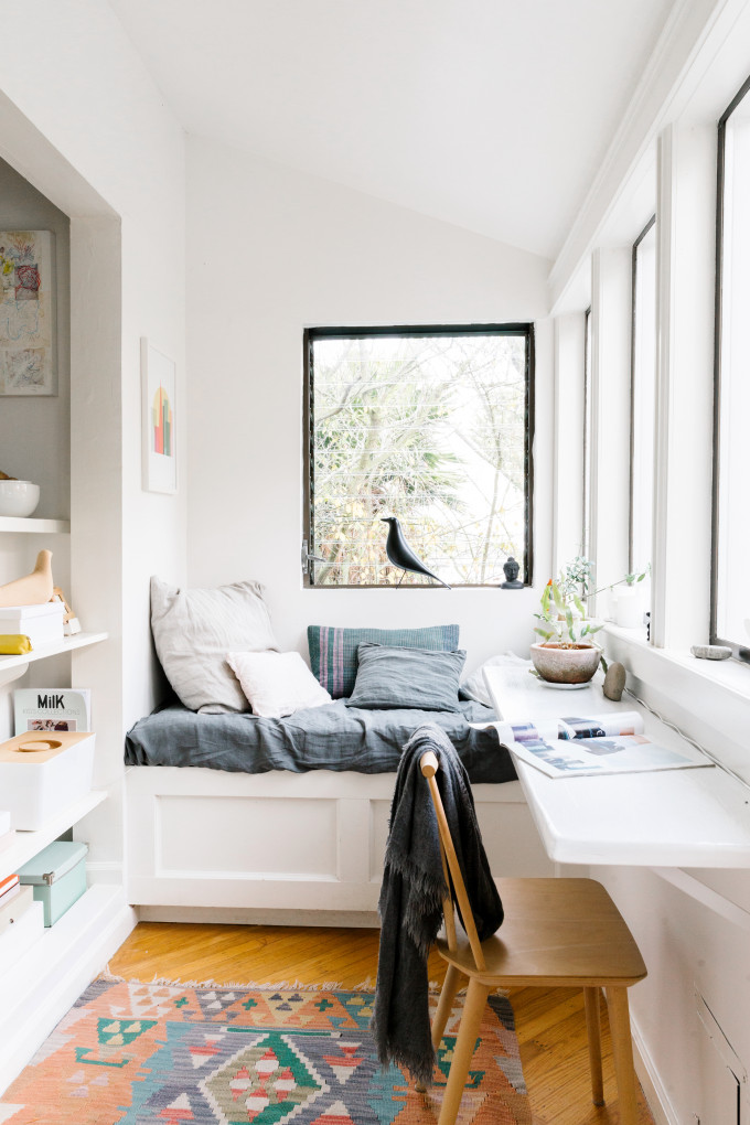 small reading nook built in bench seat in white glass windows modern wood chair medium toned wood floors multicolored area rug
