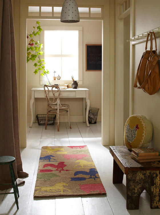 small reading nook in hallway shabby wood bench animal print runner carpet white table shabby white chair greenery centered glass window