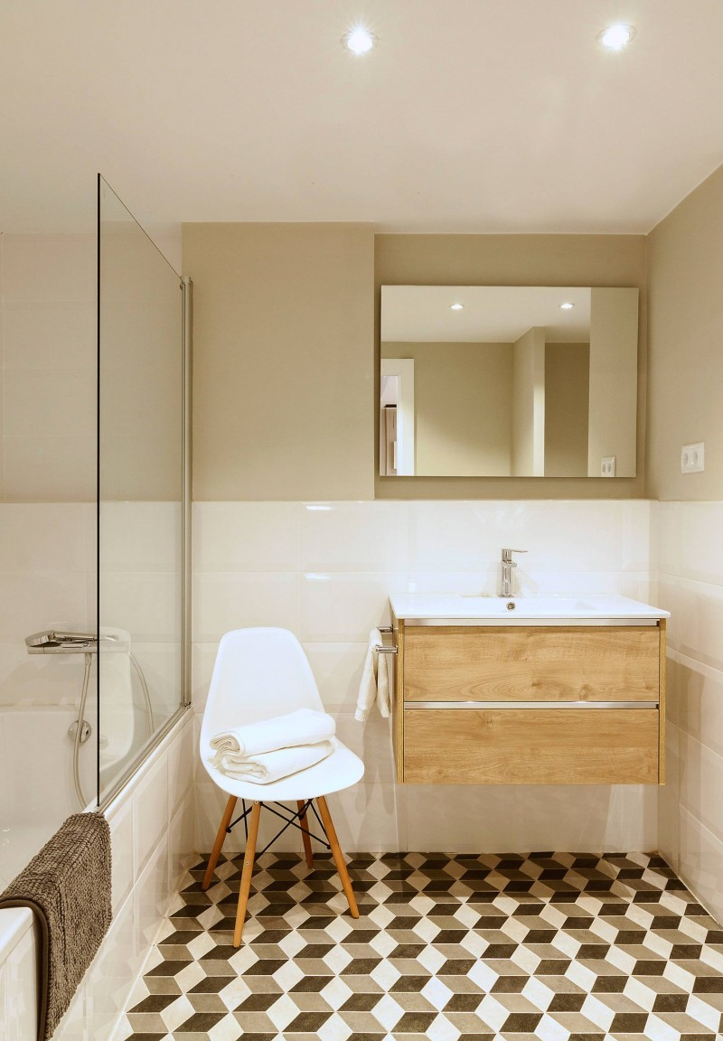 stunning Scandinavian bathroom patterned tile floors white Scandinavian styled chair with angled wood legs floating light wood vanity frameless mirror built in bathtub with clear glass panel