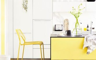 sunshine schemed kitchen counter with black top yellow bar stool with backrest white coated kitchen cabinets hanging greenery