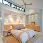 Tropical Bedroom Idea Top Glass Windows With Black Frames Floating Light Wood Bedside Tables A Pair Of Wall Mount Lamps Light Wood Desser Light Wood Toned Carpet
