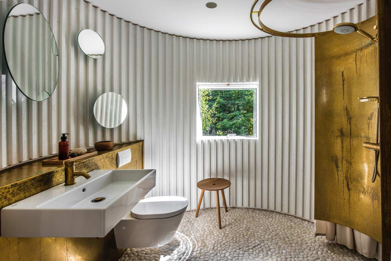 unique round Scandinavian bathroom with textured walls gold toned bathroom vanity modern white sink wall mounted toilet in white small stoned floors round shaped walk in shower with circular curt