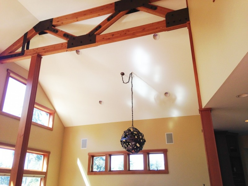 wood panelling with hard metal accents metal pendant mounted on ceiling cream painted walls wood framed interior windows