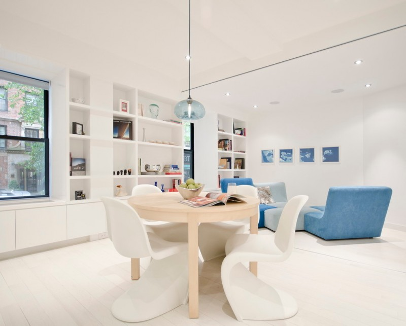 Danish inspired interior in white modern white breakfast nook with light wood dining table muted blue sofas recessed shelves in white modern glass pendant in light blue
