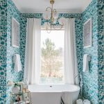 Classy Bathroom Deep White Bathtub Gold Toned Rack Blue Wallpaper With Floral Motifs Brass Chandelier With White Bulbs White Curtains