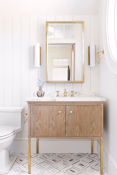 clean look bathroom idea vertical wood planks wall geometric tiled floors marble top bathroom vanity with wood cabinets white toilet brass framed mirror