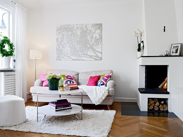 dominant white living room white sofa with colorful throw pillows white shag rug wood floors white pouch white coffee table with stainless steel construction modern fireplace