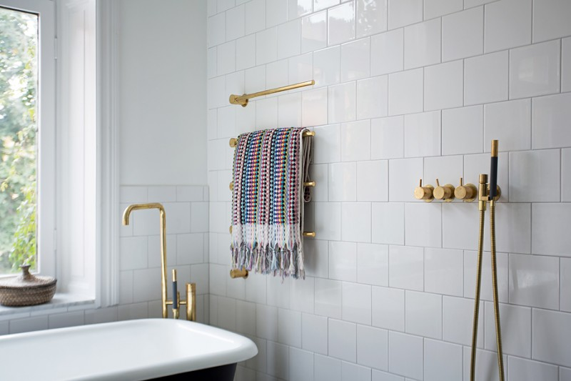 elegant and glam bathroom idea white subway ceramic tiles walls brass fixtures clawfoot tub