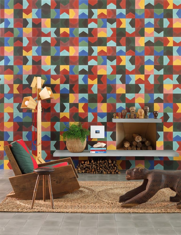 huge mosaic wall consisting vividly colors and patterns wood armchair leather top stool light wood tripod floor lamp natural fiber rug decorative wood animal statue