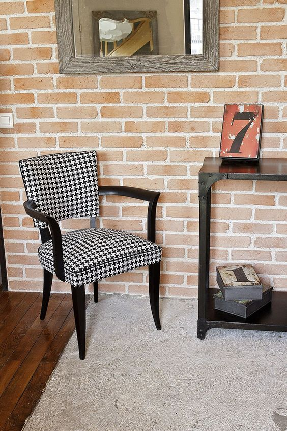 mid century modern chair with black white upholstery and black painted wood angled legs and armrests