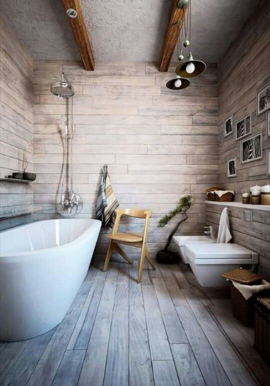 neutral toned bathroom wood plank walls and floors white bathtub wood chair wall mounted toilet in white industrial pendants