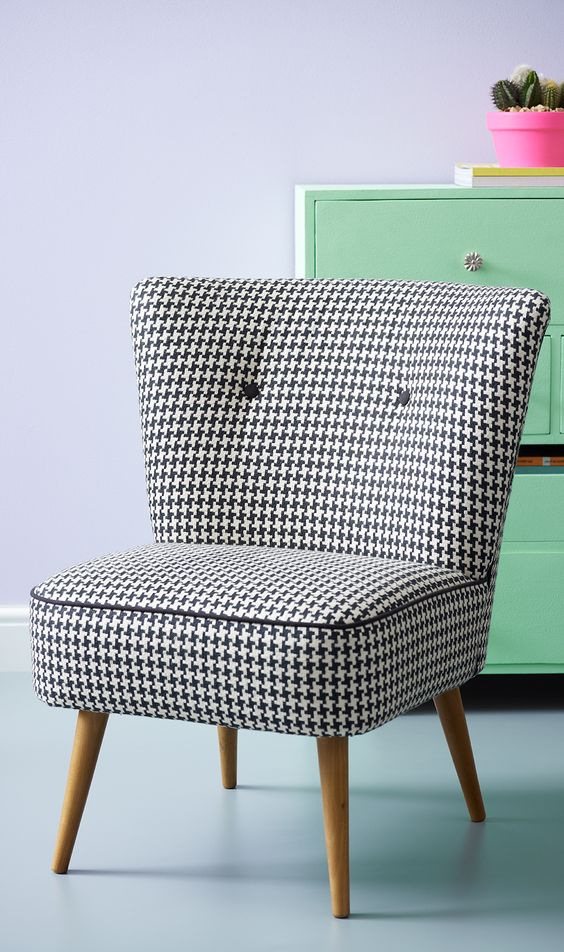 retro style chair with black white upholstery and wood angled legs