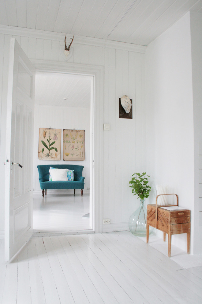 scandinavian inspired interior in white pop of colorful loveseat wooden side table houseplant on transparent glass pot white painted wood plank floors and walls