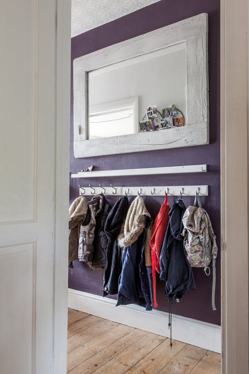 simple and small entryway solution hooks and shelf in white white framed wall mirror wood planks floors dark purple painted walls