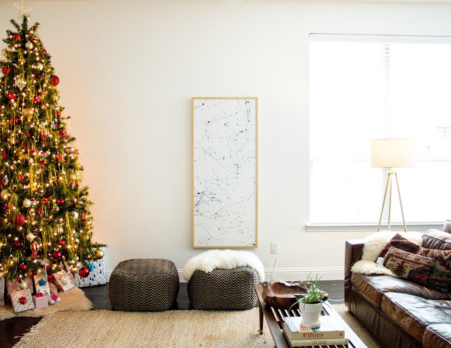 simple paint framed with light wood frames dark toned pouches Christmas tree dark leather sofa