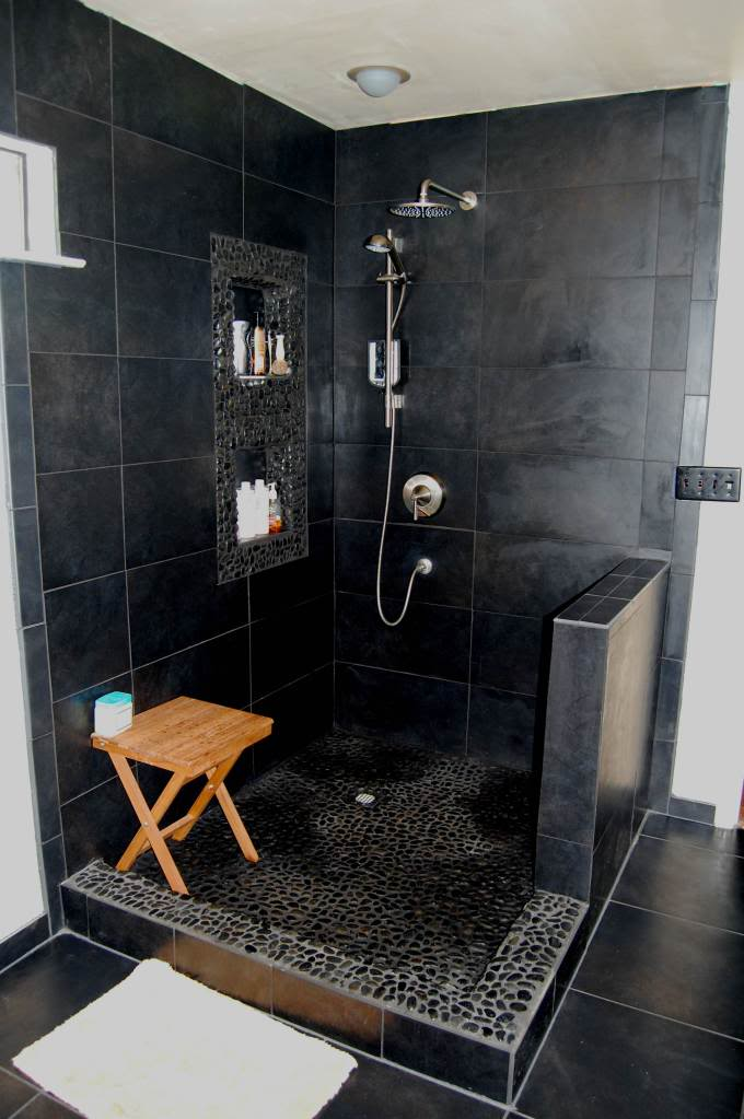 small bathroom in black black tiled walls black stoned floors wood shower bench with x base wall mounted shower fixture recessed shelves