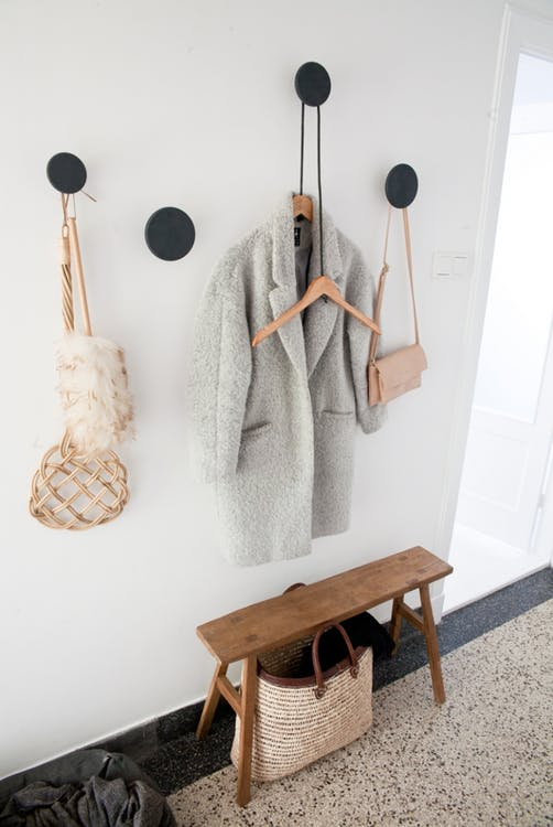 small entryway idea white walls with black polka dot holders wood bench