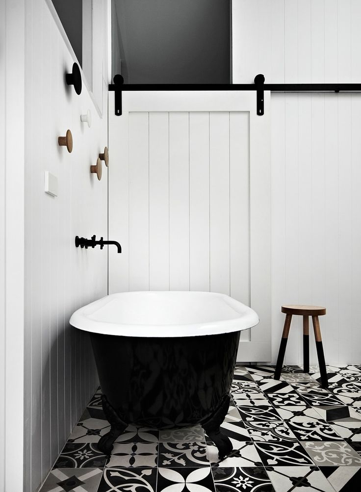 white black bathroom idea freestanding bathtub white wood siding walls white black patterned tiles flooring