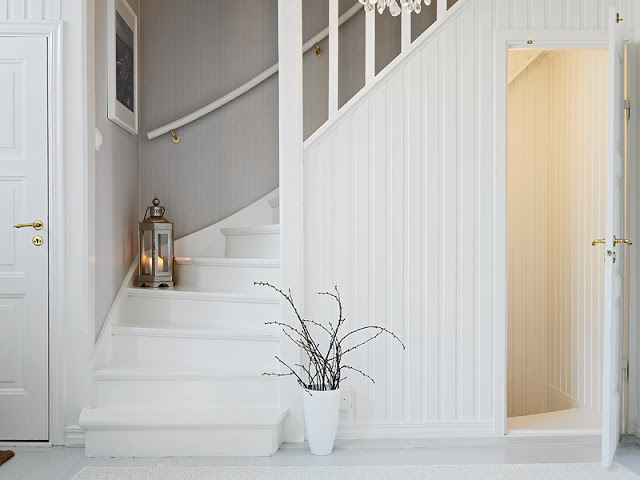 white interior staircase with white steps and white railings leave less houseplant on white pot