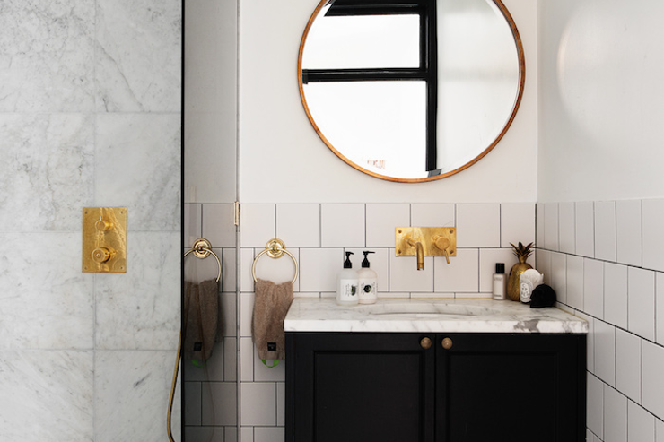 white subway tiles wall brass framed mirror in round shape marble countertop black cabinets brass sink undermount sink