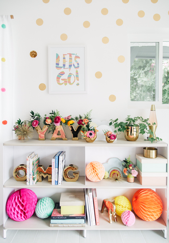 white walls with pastel polka dots white shelving unit glowing brass accessories colorful paper balls