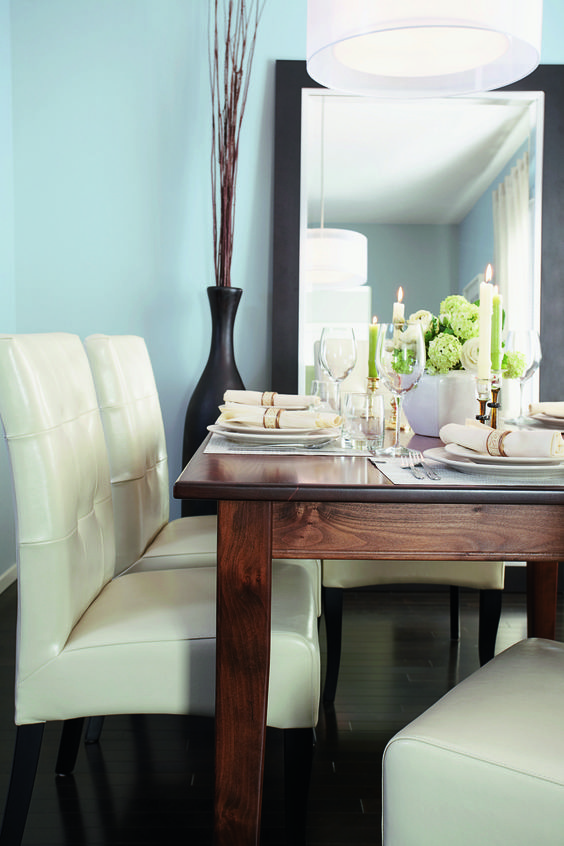 angelic blue walls broken white dining chairs wooden dining table solid black vase solid black mirror frame