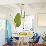 Beach Style Breakfast Nook Idea White Round Shaped Dining Table Scandinavian Styled Chairs In Blue Tropical Houseplant Decorative Surfing Board Terracotta Tiled Floors Modern Pendants