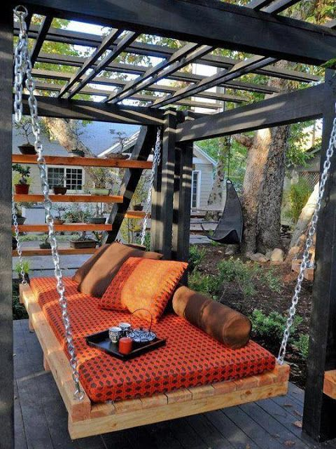 black finish pergola with pallet swing colorful mattress and throw pillows