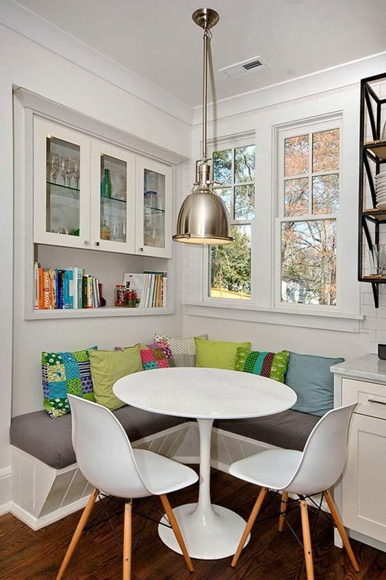 corner cabinets and bookshelves in small breakfast nook modern pendant with metal lampshade built in corner bench mutliple colored throw pillows white Scandinavian style chairs white dining table