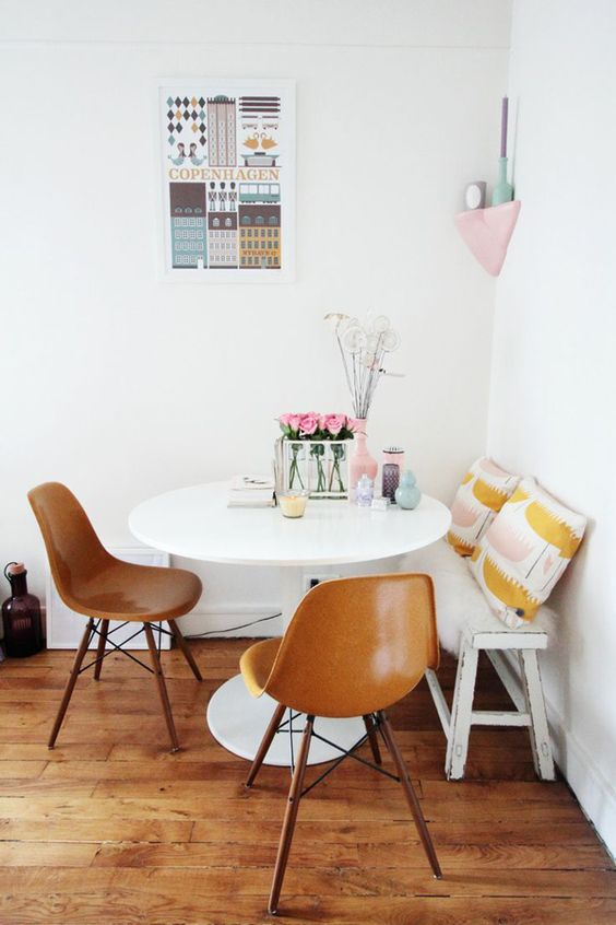 entertaining breakfast nook idea white round dining table brown Scandinavian style dining chairs with wood angled legs shabbier white bench seat with mustard throw pillows