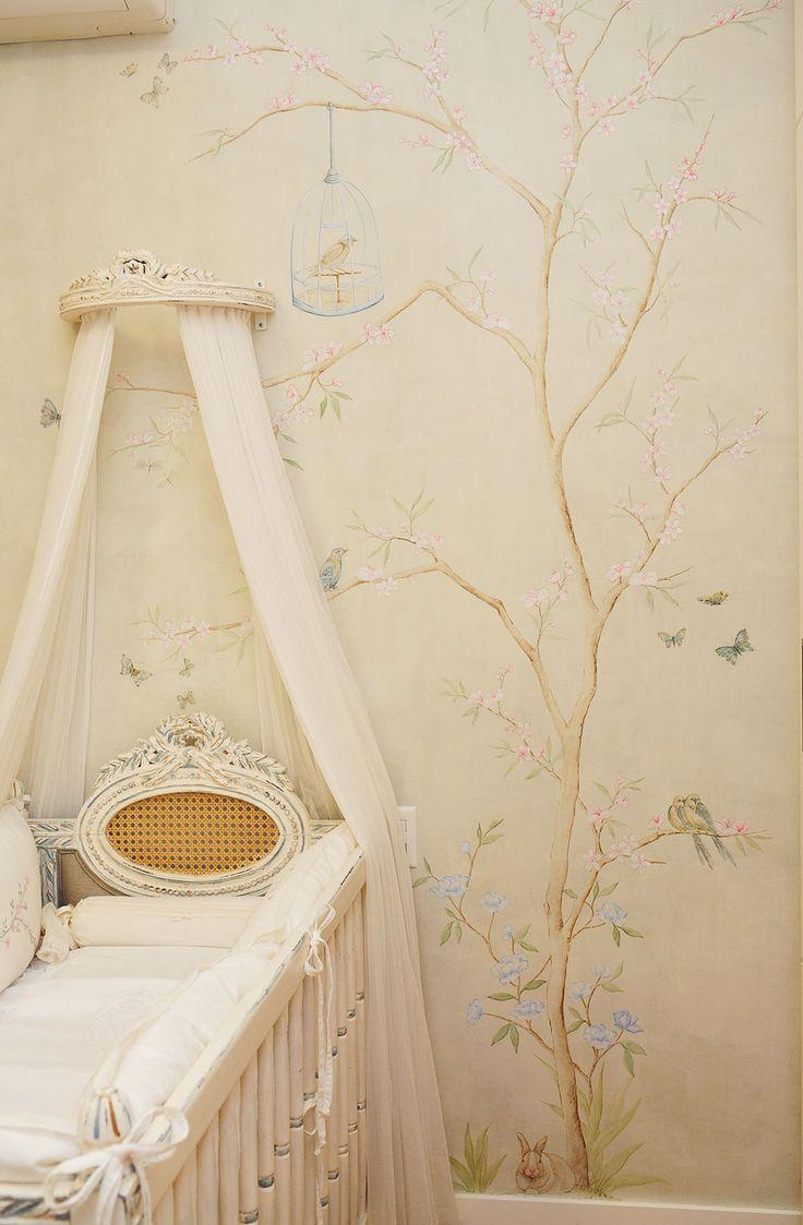 floral themed nursery room tree wallpaper with animated bird decors light cream bed canopy's curtains light cream baby crib white bed linen