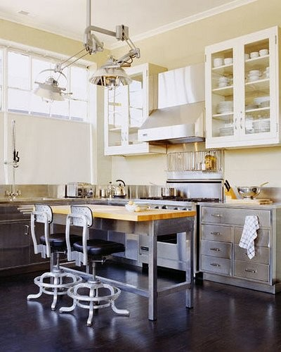 industrial eat in kitchen with ultra modern light fixture metal island with blockbutcher worktop metal vintage chairs with black leather seater metal kitchen cabinets upper display units