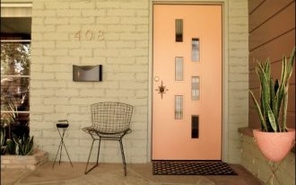 light orange front door with accent glass windows black rubber doormat black wire made chair black wall mounted mailbox light orange planter