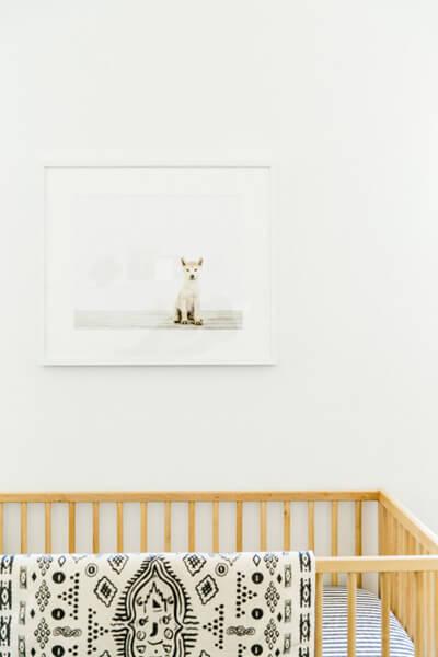 minimalist nursery room light wood baby crib patterned blanket minimalist artwork on wall