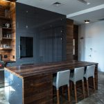 Modern Industrial Kitchen With Masculine Touch Flat Paneled Metal Cabinets Dark Wood Island With Metallic Accent Modern Stools In Gray