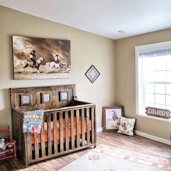 raw rustic nursery room dark wood finishing baby crib darker wood floors cowboy picture on wall