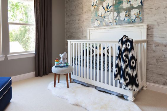 rustic nursery room design with modern mountain man vibe wallpaper white baby crib flufy shag rug in white smaller stool
