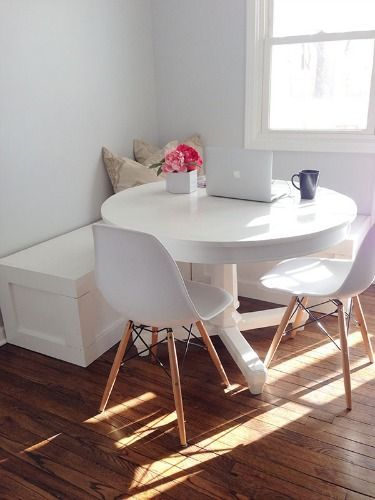 simple small breakfast nook idea white round dining table scandinavian style dining chairs with angled wood legs white bench seat wood floors