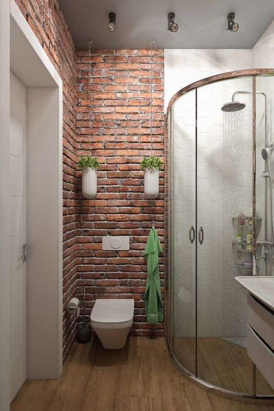 small bathroom idea brick walls with wall mounted houseplants wall mounted toilet in white walk in shower space with semi curved glass door wood floors