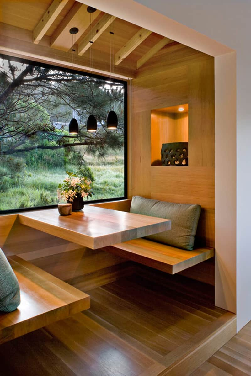 small cabin's breakfast nook idea floating wood table floating wood bench seats larger glass window with black frame wood ceilings wood walls wood floors