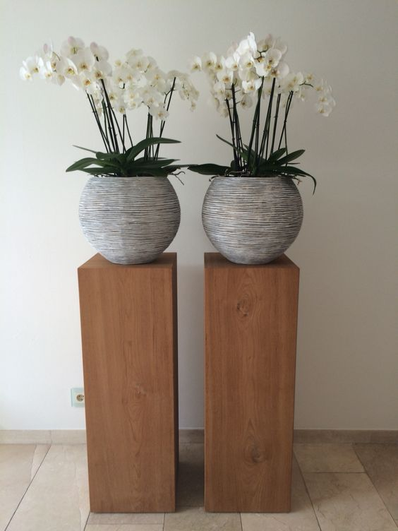 textured gray concrete planters with log supports