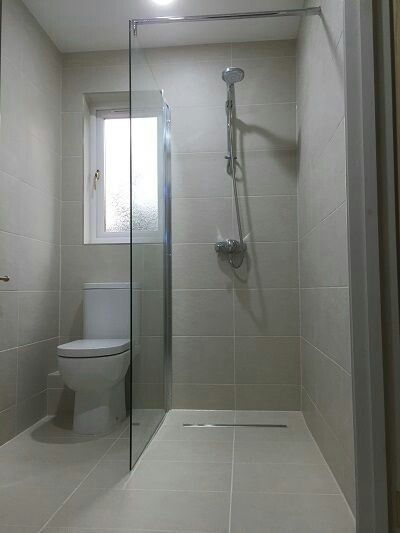 two chamber small bathroom design clear glass divider walk in shower space white toilet blurry glass window light gray ceramic tiled walls and floors