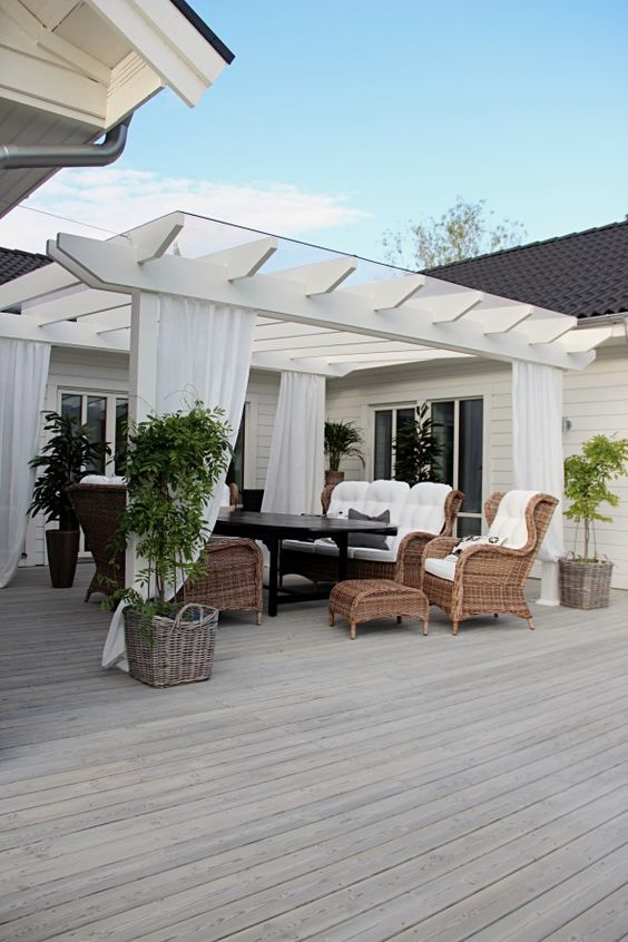 white pergola with dramatic white curtains wicker furnishing pieces