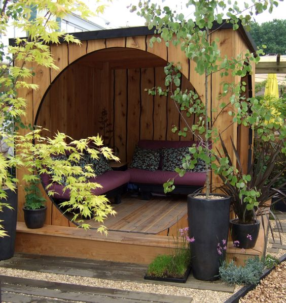 wood pergola pod with curved door and seating area inside