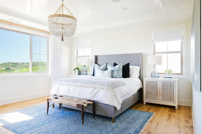 beach style bedroom design blue textile rug light wood floors modern bed frame with blue headboard white bedding treatment sun bleached nightstand with lattice door panel