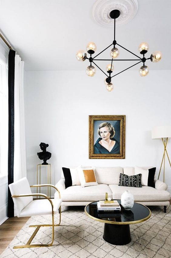 black and white living room with gold glam white sofa round top black coffee table with gold line accent modern white chair with gold highlights white area rug with modern pattern