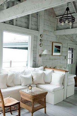 chic rustic farmhouse living room L shaped couch in white white throw pillows woven coffee table with glass top wooden chair whitewashed walls and ceilings