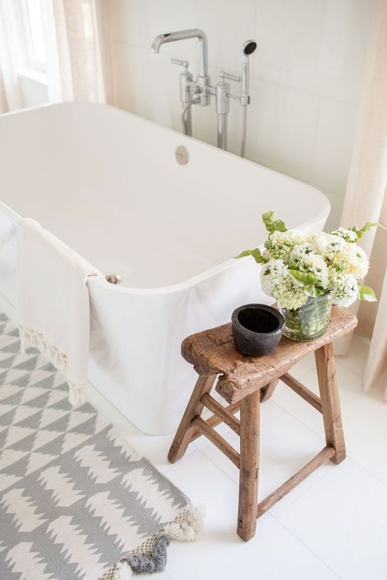 clean look and modern farmhouse bathroom white bathtub light gray white shower mat aged wood bench as the side table
